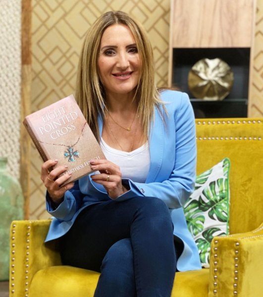 Television host Claire holding a copy of Eight Pointed Cross
